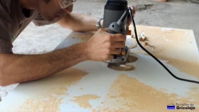 fresando el hueco para insertar la fresadora en la mesa