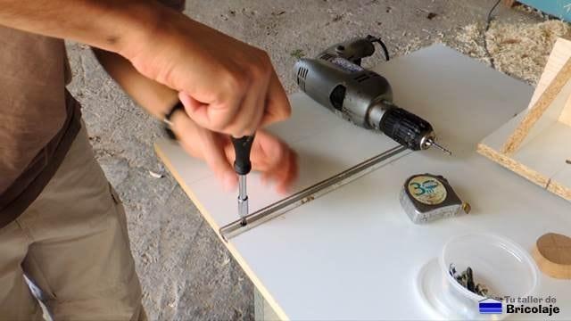 atornillando los carriles en la mesa para la fresadora de madera