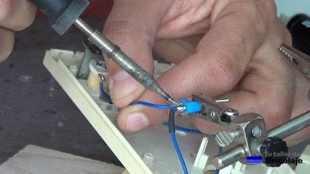 soldando los cables al interruptor de palanca para anular o activar el timbre del portero eléctrico