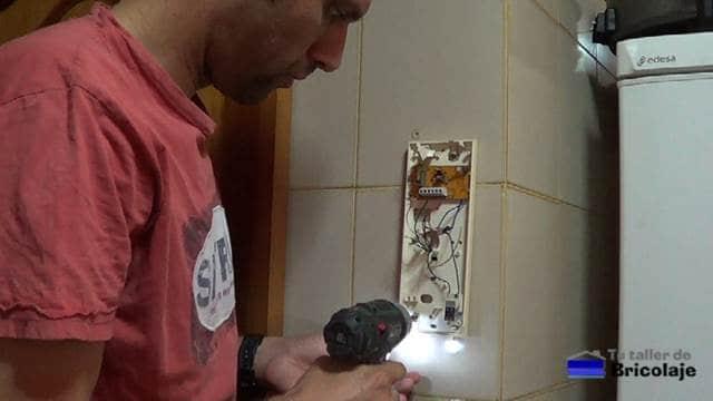 sujetando la base con tornillos a la pared