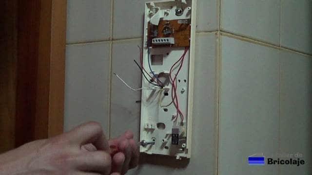 retirando los tornillos para poder extraer la base del telefonillo de la pared