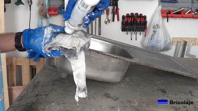 aplicando limpiador de acero inoxidable en un trapo humedecido