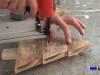 sujetando las piezas que formarán el árbol de navidad con tachas o clavos