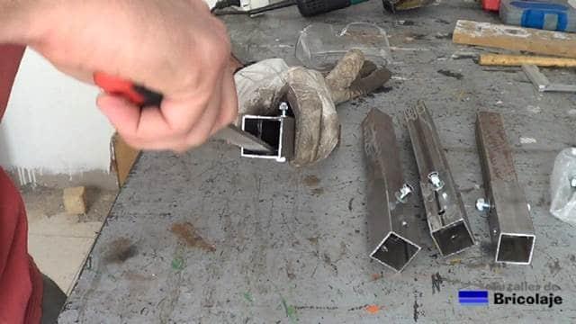 eliminando las rebabas interiores del cuadradillo generadas por la broca de hierro al entrar en el material