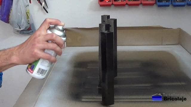pintando con spray las nuevas patas para aumentar de altura el banco de trabajo