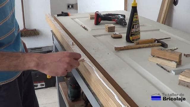 repartiendo la cola en el listón para unirlo al lateral de la puerta prefabricada