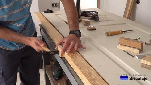 insertando el listón de madera en el lateral de la puerta