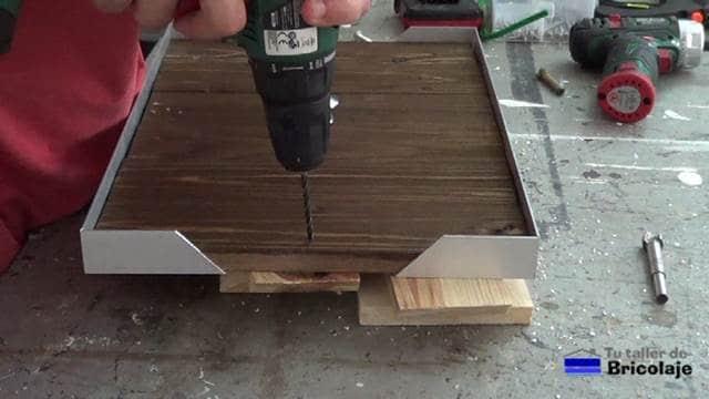 perforando para colocar los pomos para sujetar la bandeja de comida