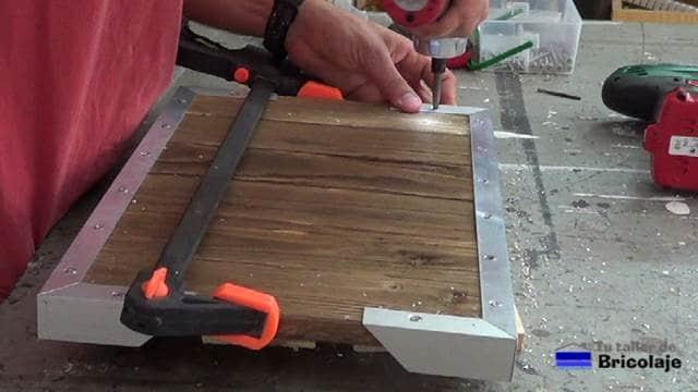 atornillando el ángulo a la madera de palé