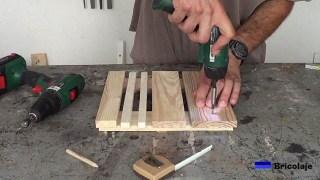 colocando el tornillo para sujetar la estructura de la base con ruedas para macetas