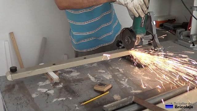 cortando hierro reciclado para fabricar la burra o caballete metálico regulable en altura