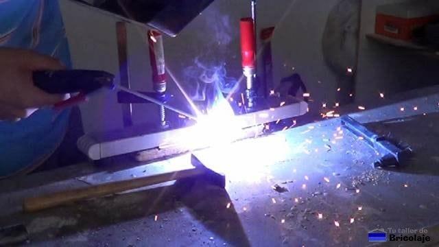 soldando los trozos de hierro para formar una de las patas de la burra o caballete regulable en altura