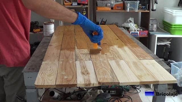 embarnizando con rodillo de espuma el cabecero de madera de palets