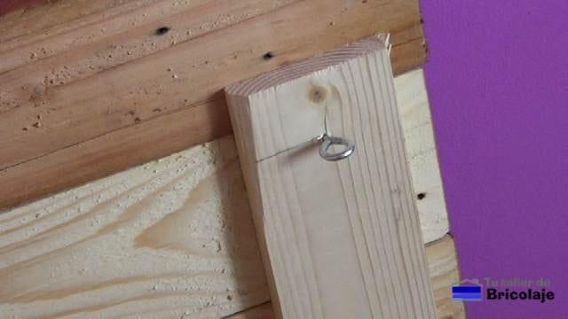 colocando unos cancamos a la trasera del cabecero de palets para poder colgarlo en la pared