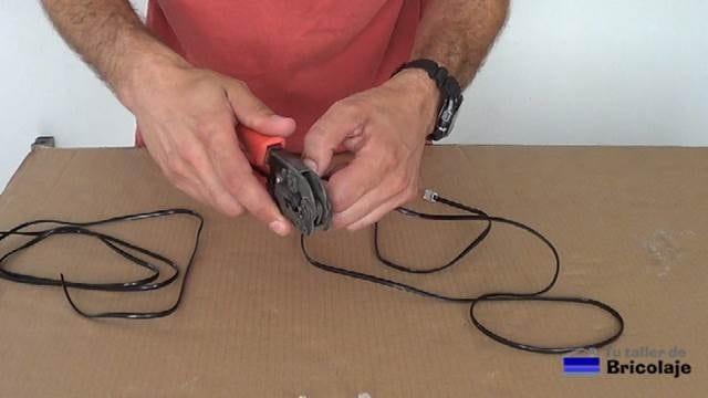 retirando la cubierta del cable de teléfono con la crimpadora