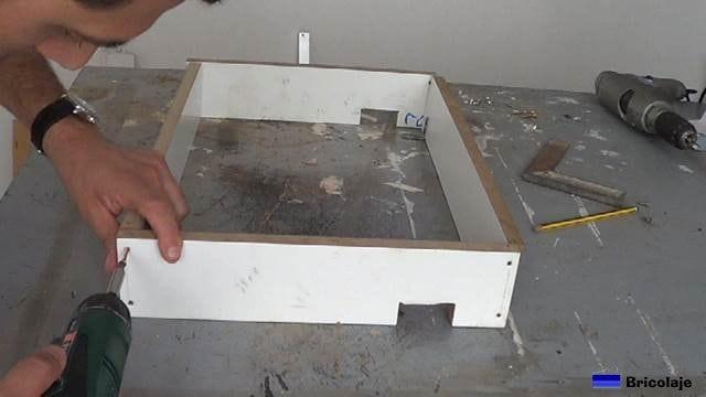 atornillando la estructura que formará la caja de registro