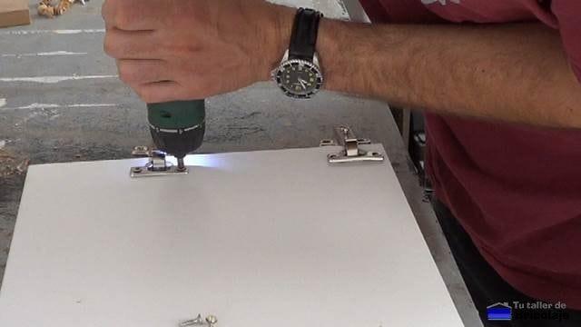 atornillando las bisagras en la puerta de la caja de registro
