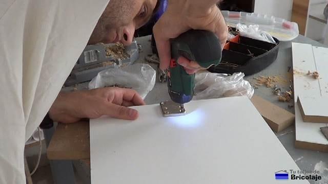 atornillando la cerradura a la puerta de la caja de registro