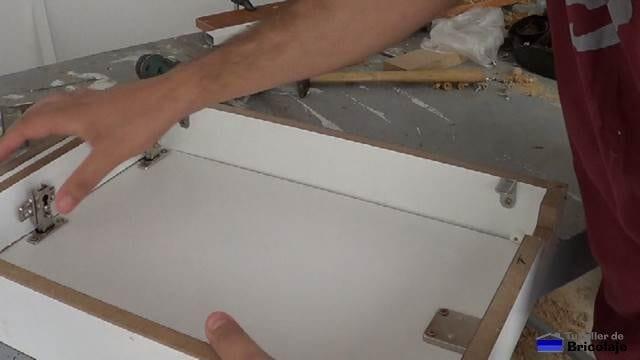 colocando la puerta en la estructura de la caja de registro de madera