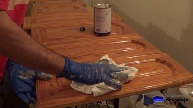 limpiando la superficie lijada de las puertas de cocina con aguarrás o disolvente