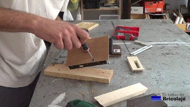 atornillando el disco duro al cartón piedra