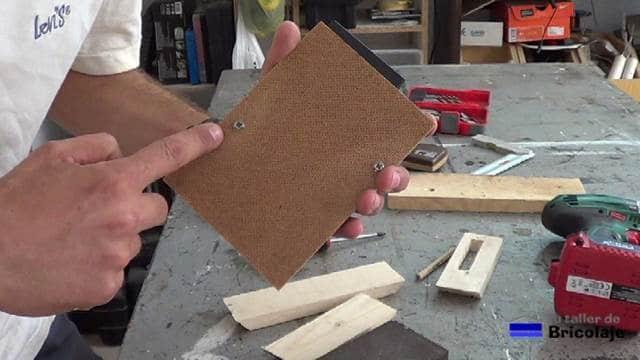sujetando el disco duro al cartón piedra mediante tornillos