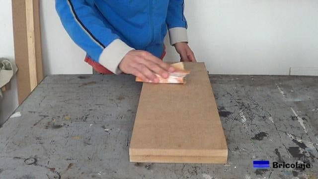 lijando la madera con lija de grano fino