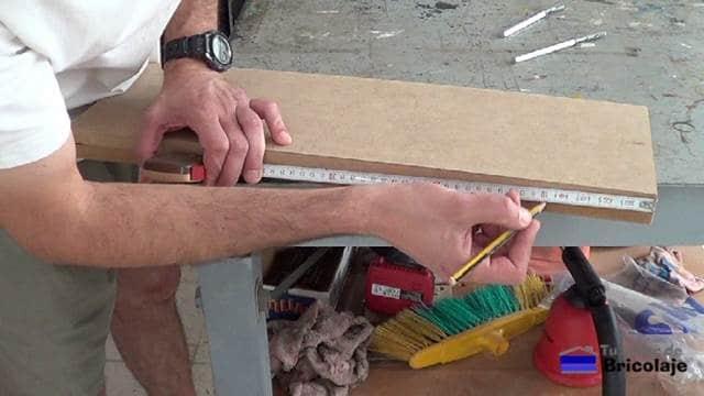 midiendo el lugar donde perforar la balda, estante o repisa