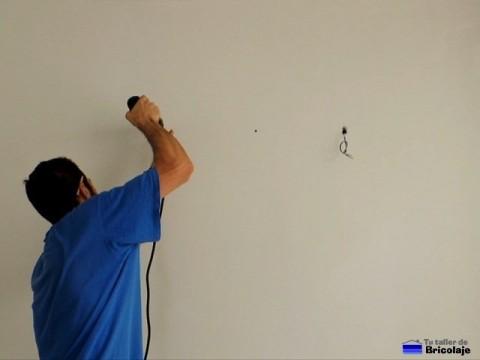 taladrando la pared para colocar el soporte del fluorescente