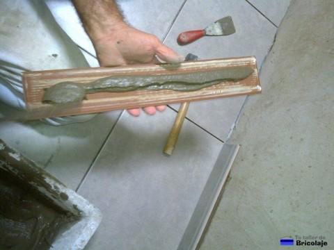 echando el cemento cola en el rodapié