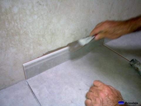 eliminando el exceso de cemento cola con la espátula