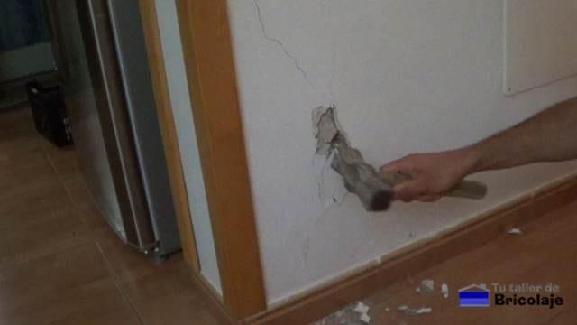 quitando con el martillo el cemento suelto debido a la grieta