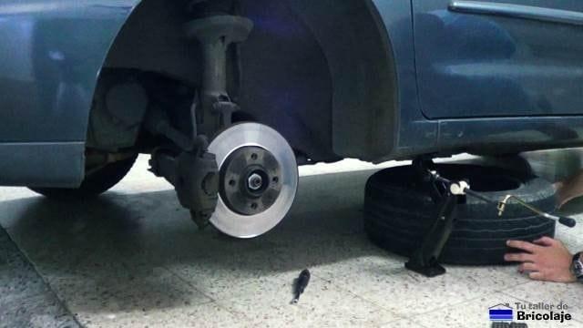 quitando la rueda del coche para poder solucionar el parachoques o paragolpes suelto