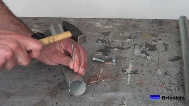 realizando una hendidura con una tacha o clavo de acero sobre el tubo de 40 mm de diámetro