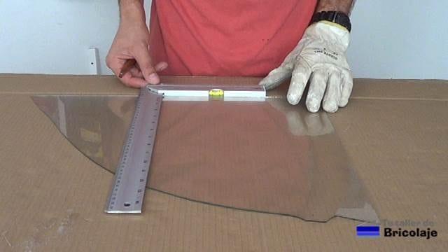 usando la escuadra para realizar un corte recto en el vidrio o cristal