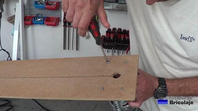 sujetando la fresadora o router a la plantilla mediante los tornillos