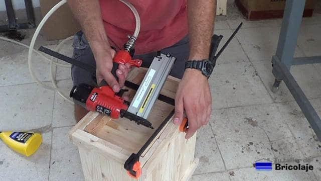 sujetando el suelo del cubo de basura con la clavadora neumática
