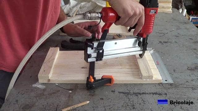 clavando tachas o clavos para sujetar las piezas que formarán el lateral del cubo de basura