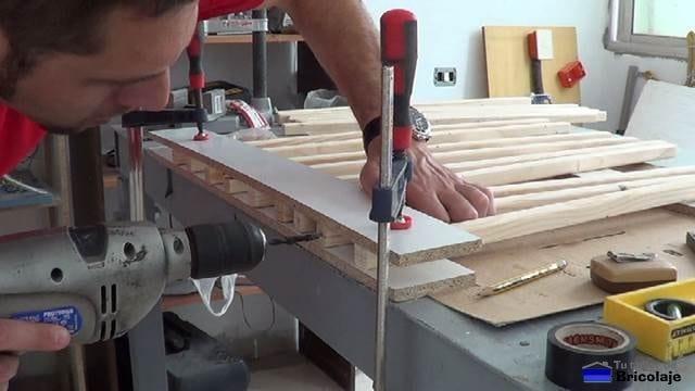 taladrando los barrotes que formarán la cuna colecho para insertar los tarugos