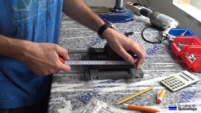 centrando la mordaza de taladro sobre las correderas de cajón en la base