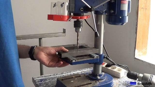 perforando la base para sujetarlo a la mesa del taladro de columna o soporte para taladro