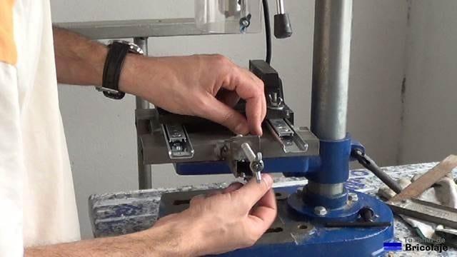 sujetando la escopleadora casera a la mesa del taladro de columna