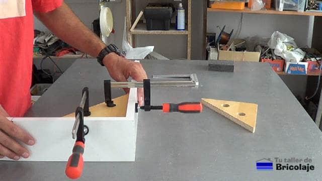 sujetando y escuadrando dos trozos de madera a unir mediante las escuadras