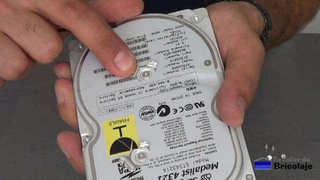 tornillos ocultos bajo la pegatina de información técnica del disco duro