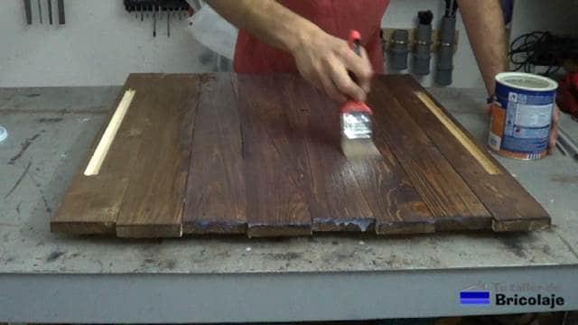 aplicando el barniz incoloro sobre el tinte aplicado a la madera de palet
