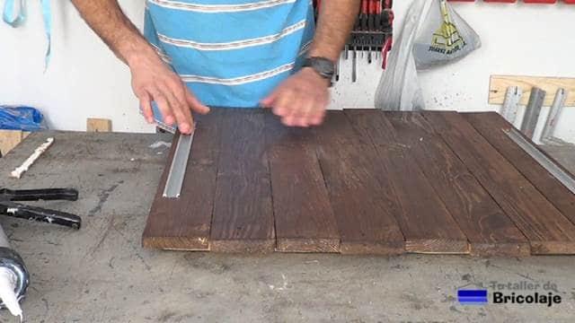 pegando los perfiles de aluminio para las tiras de leds a la madera de palets