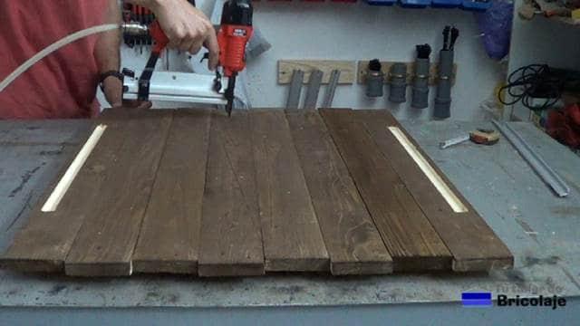 clavando las maderas para realizar el espejo con madera de palets y led