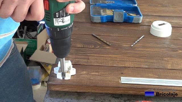 atornillando la base del interruptor a la madera de palet