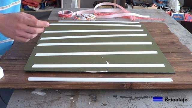 retirando las protecciones de la cinta de doble cara Tesa para pegar el espejo a la madera de palets