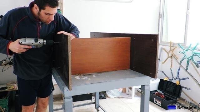 atornillando el lateral a la balda para hacer una estantería de madera